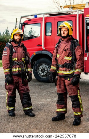 Portrait of two firemen standing next to fire truck at base. - stock photo
