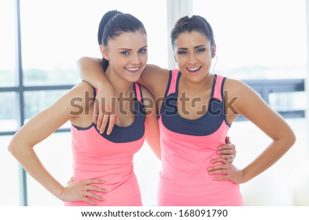 Portrait of two fit young women smiling in a bright exercise room - stock photo
