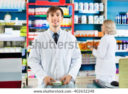 Portrait of two friendly charming pharmacists working in modern farmacy