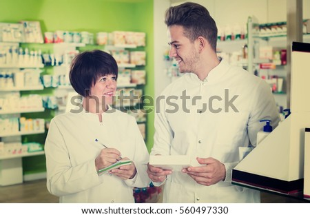 Portrait of two friendly pharmacists working in modern pharmacy