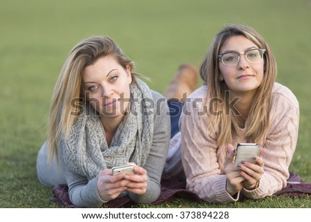 Portrait of two friends lying down on their stomach on grass holding smartphone - stock photo
