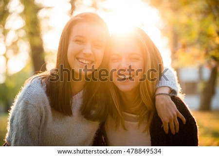 Portrait of two friends -  teenagers, outdoor in autumn at sunset