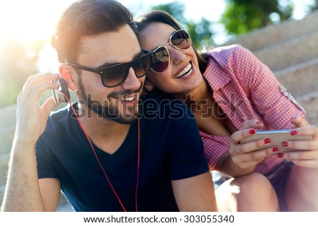 Portrait of two friends using mobile phone and listening to music in the street.
