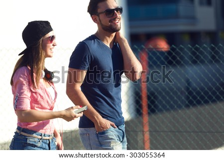Portrait of two friends using mobile phone and listening to music in the street. - stock photo