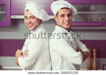 Portrait of two funny working men in cook uniform posing in modern kitchen. Indoor shot - stock photo