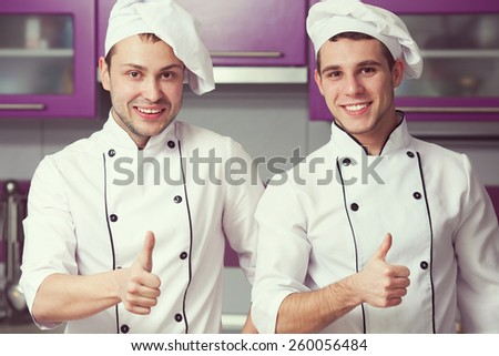 Portrait of two funny working men in cook uniform showing OK sign (thumbs up) and posing in modern kitchen together. Close up. Indoor shot - stock photo