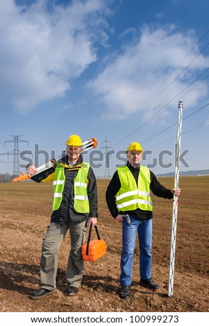 Portrait of two geodesist holding measuring equipment on construction site