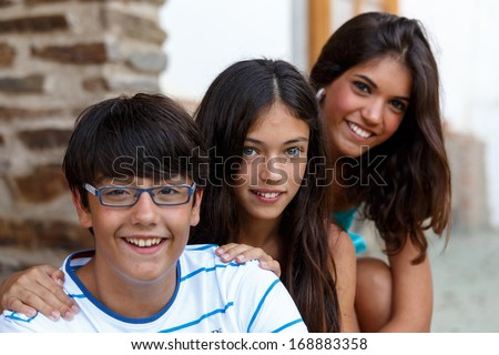 Portrait of two girls and a boy, all Smiling At Camera