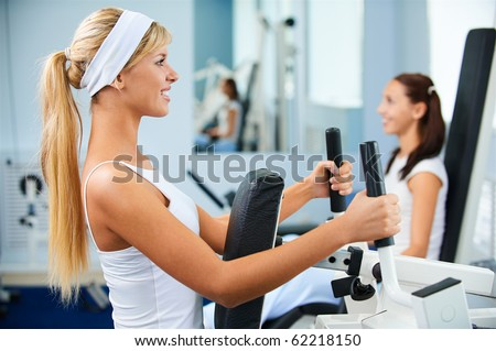 portrait of two girls exercising in gym on various machines - stock photo