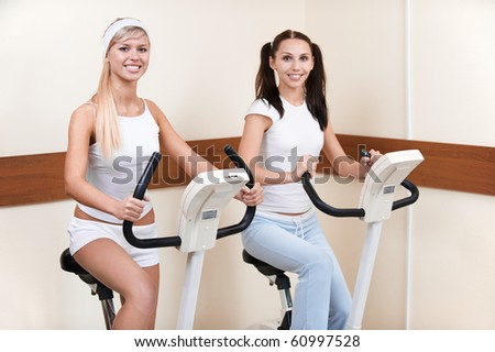 portrait of two girls exercising on excercise bikes in gym