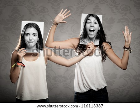 portrait of two girls holding a photography in front of face