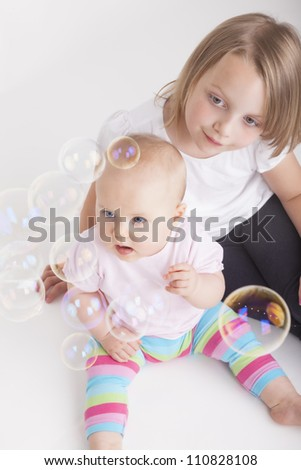 portrait of two girls playing with soap bubbles. studio shot with a white background - stock photo