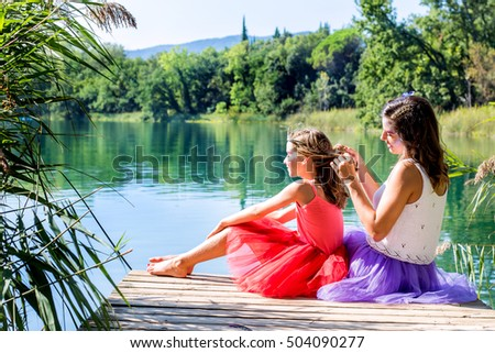Portrait of two girls relaxing on wooden deck next to lake.Girls dressed up in colorful  dresses.