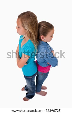 Portrait of two girls standing back to back against a white background - stock photo