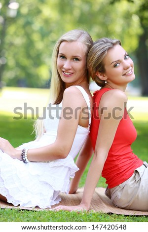 Portrait of two girls who are having pretty much fun in the park. They are talking, discussing, laughing at each other and have a really good time