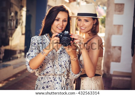Portrait of two good looking sisters looking at the camera screen during sightseeing in foreign country or city.