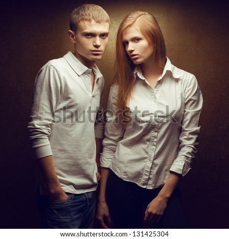 Portrait of two gorgeous red-haired (ginger) fashion twins in white shirts posing over golden background together. Studio shot. - stock photo