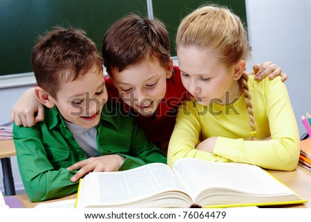 Portrait of two guys and girl reading book in classroom - stock photo