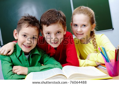 Portrait of two guys and girl sitting in classroom with open book near by - stock photo
