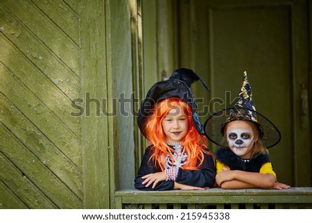 Portrait of two Halloween girls in costumes looking at camera - stock photo