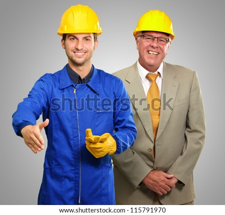 Portrait Of Two Happy Architect Engineers On Gray Background - stock photo