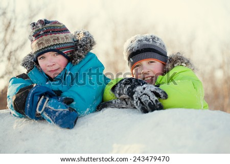 Portrait of two happy brothers in winter clothes, smiling boys on a walk in park, outdoor - stock photo