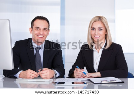 Portrait Of Two Happy Business Colleagues At Office Working Together - stock photo