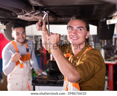 Portrait of two happy car mechanics at workshop at work - stock photo