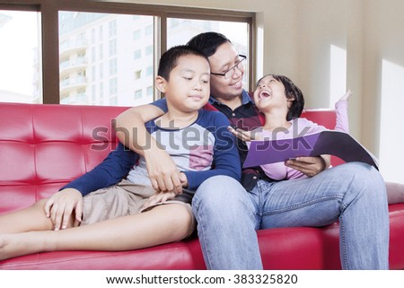 Portrait of two happy children reading a book with their father on the sofa, shot at home