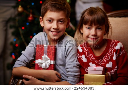Portrait of two happy children with Christmas gifts looking at camera