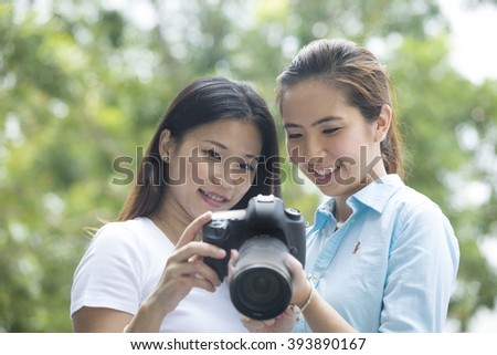 Portrait of two happy female, Asian friends taking photos with a DSLR camera. Chinese Women, girlfriends having fun shooting photos with a camera in the city.