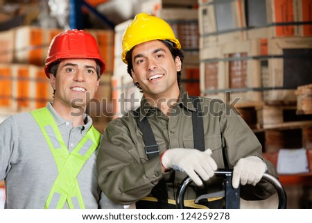 Portrait of two happy foremen wearing hardhats at warehouse - stock photo
