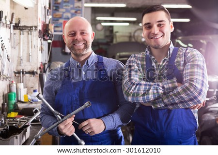 Portrait of two happy garage workmen near facilities