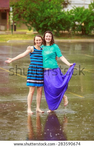 Portrait of two happy girl friends jumping in puddles during the rain thunderstorm on a bright summer day outside, sports recreation leisure concept, friendship