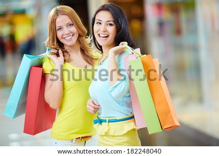 Portrait of two happy girls with paperbags looking at camera - stock photo