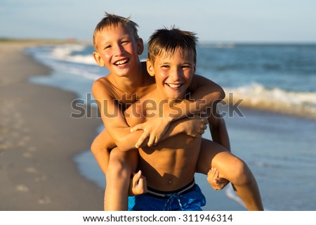 Portrait of two happy kids playing on the beach on summer vacation.