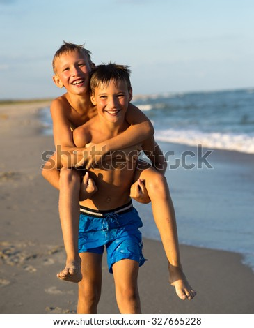Portrait of two happy kids playing on the beach on summer vacation. - stock photo