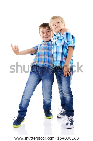Portrait of two happy little fashion boys in checked shirts and blue jeans isolated on a white background