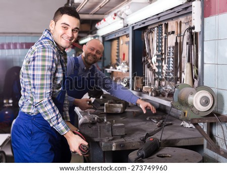 Portrait of two happy mechanics working in a service center  - stock photo