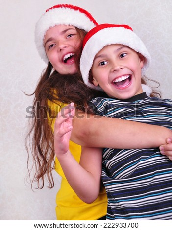 portrait of two happy playful children with Santa Claus red hats. Christmas, New Year celebration concept. Focus is on the boy - stock photo