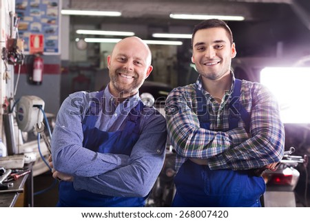 Portrait of two happy professional car mechanics at garage - stock photo