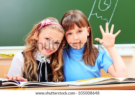 Portrait of two happy schoolgirls in a classroom. - stock photo