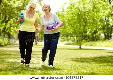 Portrait of two happy senior females walking down green grass