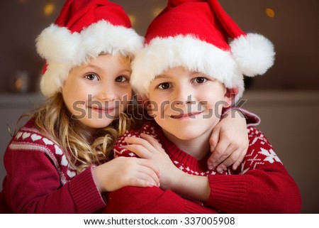 Portrait of two happy siblings in red Santa's hats