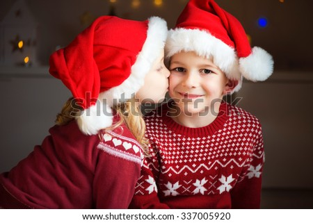 Portrait of two happy siblings in red Santa's hats  - stock photo