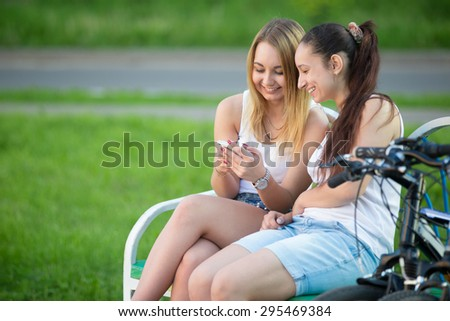 Portrait of two happy smiling beautiful young women friends wearing casual clothes sitting on park bench on summer day, having good time together, using app on smartphone, copy space