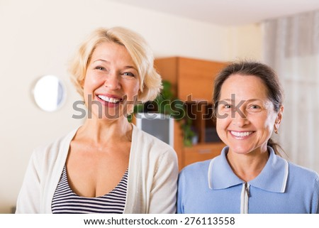 Portrait of two happy smiling female pensioners at home - stock photo