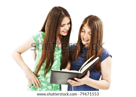 Portrait of two happy student girls reading the book. All on white background. - stock photo