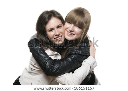 Portrait of two happy woman, blond and brunette, with black and white leather jacket, isolated on white background