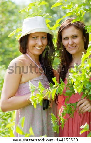 portrait of two happy women in spring  garden - stock photo